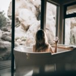 woman in white bathtub holding clear drinking glass