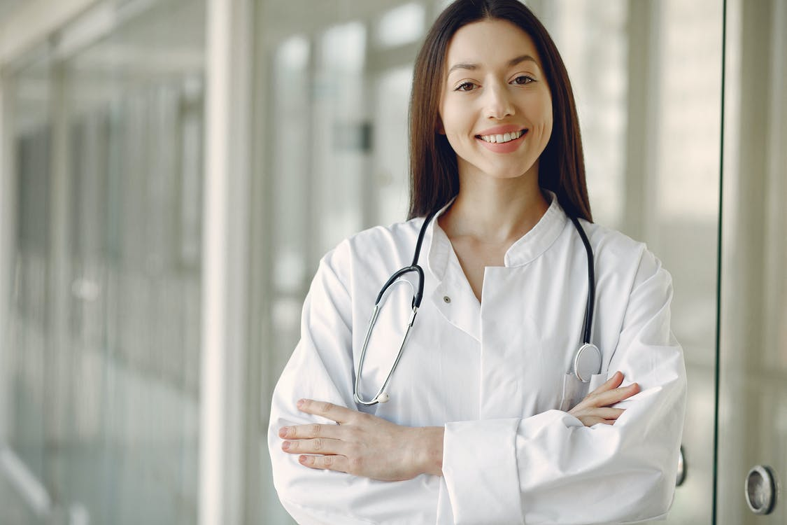 Crop doctor in medical uniform with stethoscope standing in clinic corridor